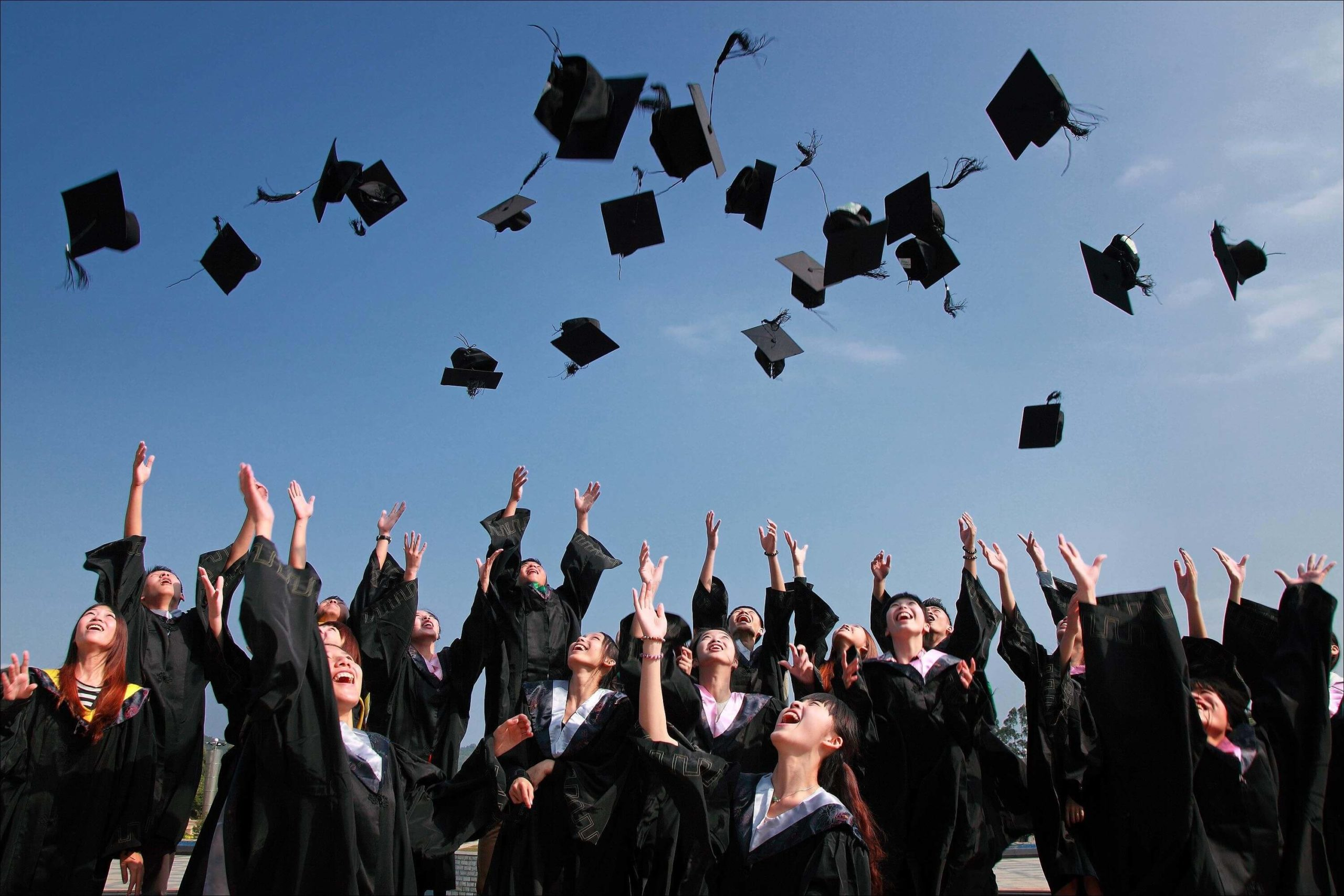 A group of graduates in black gowns throwing their mortarboard hats into the air while cheering.