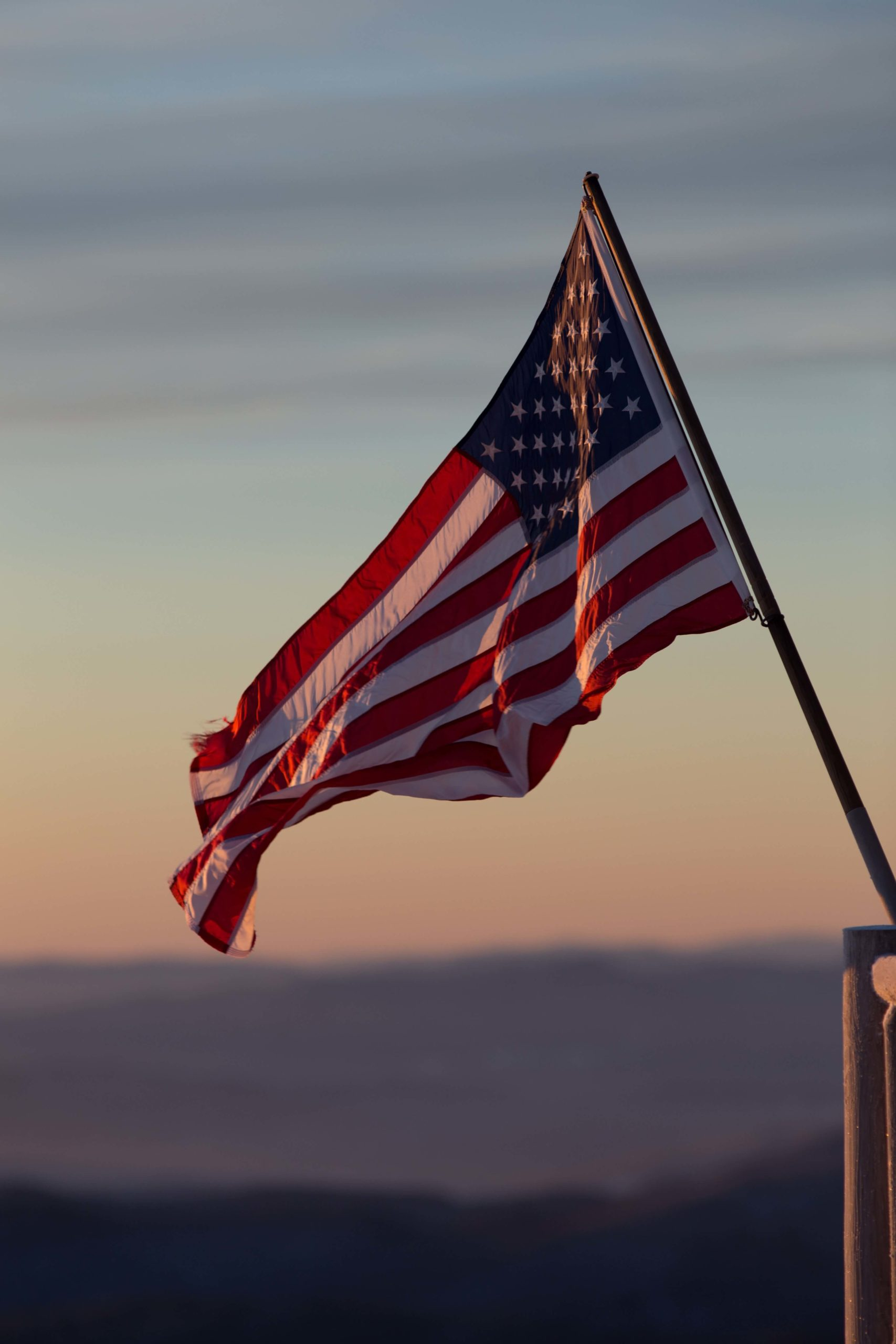 An American flag on a pole rippling in a light breeze in front of a sunset.