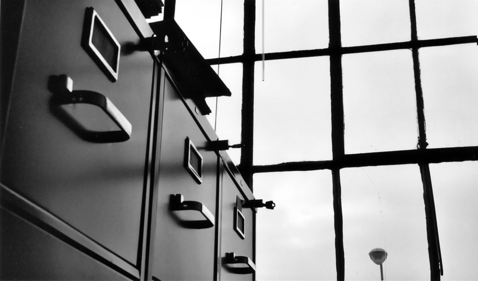 A row of file cabinets set up indoors next to large windows.