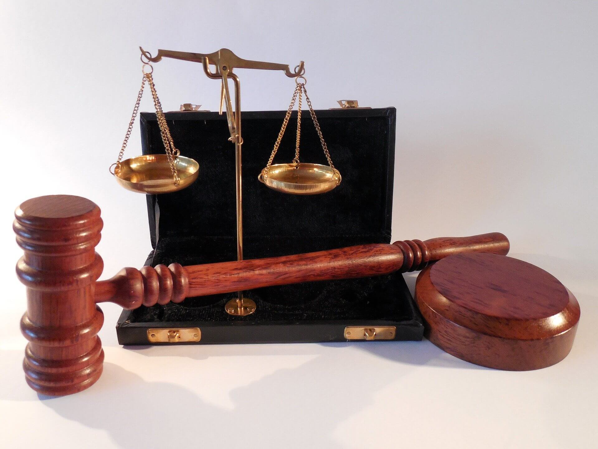 A desktop-sized model of the scales of justice sitting in a black case, along with a polished wooden gavel.