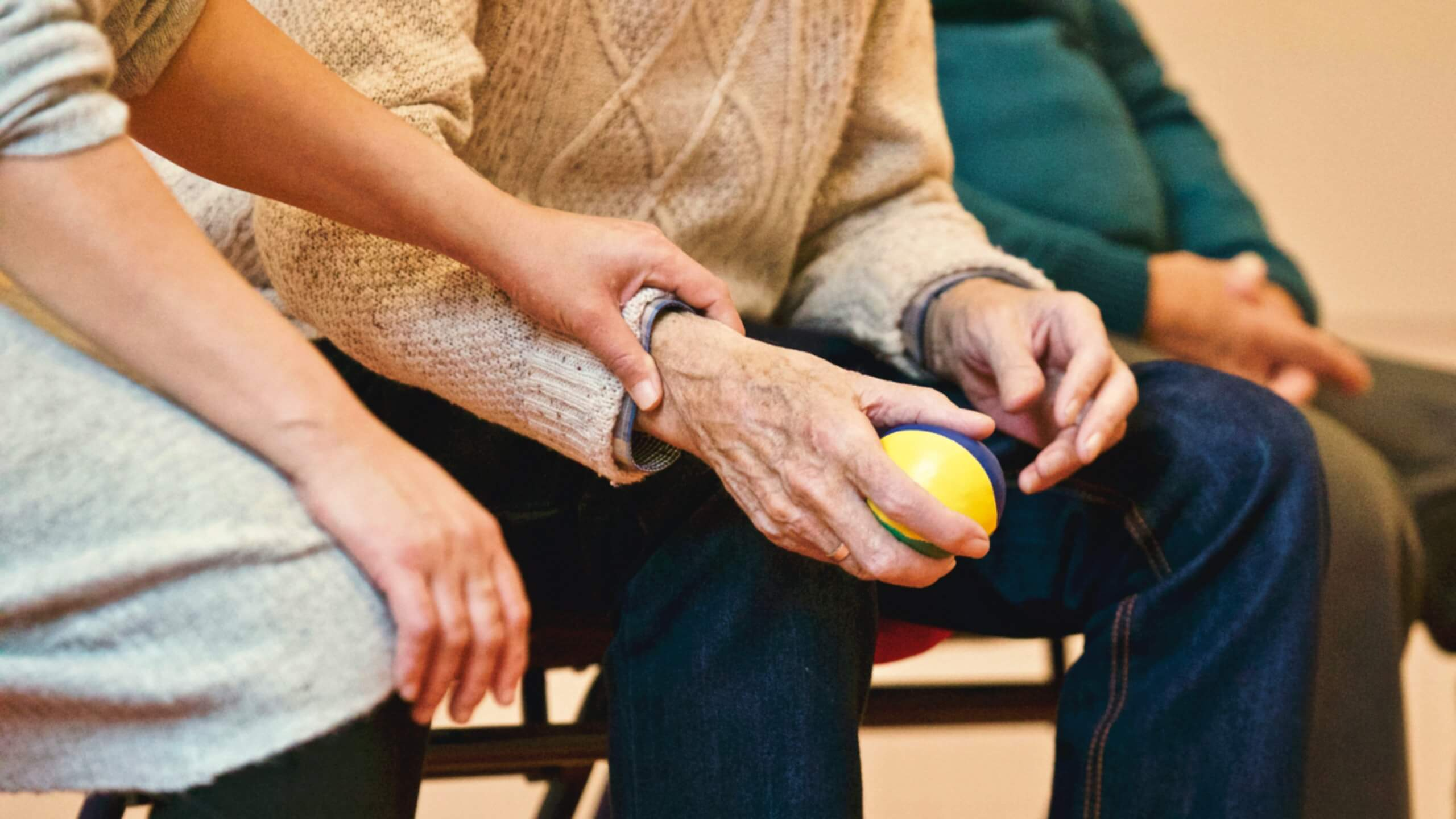 An elderly woman's hands holding a black and white stress ball, while a pair of younger hands grasp her wrist.