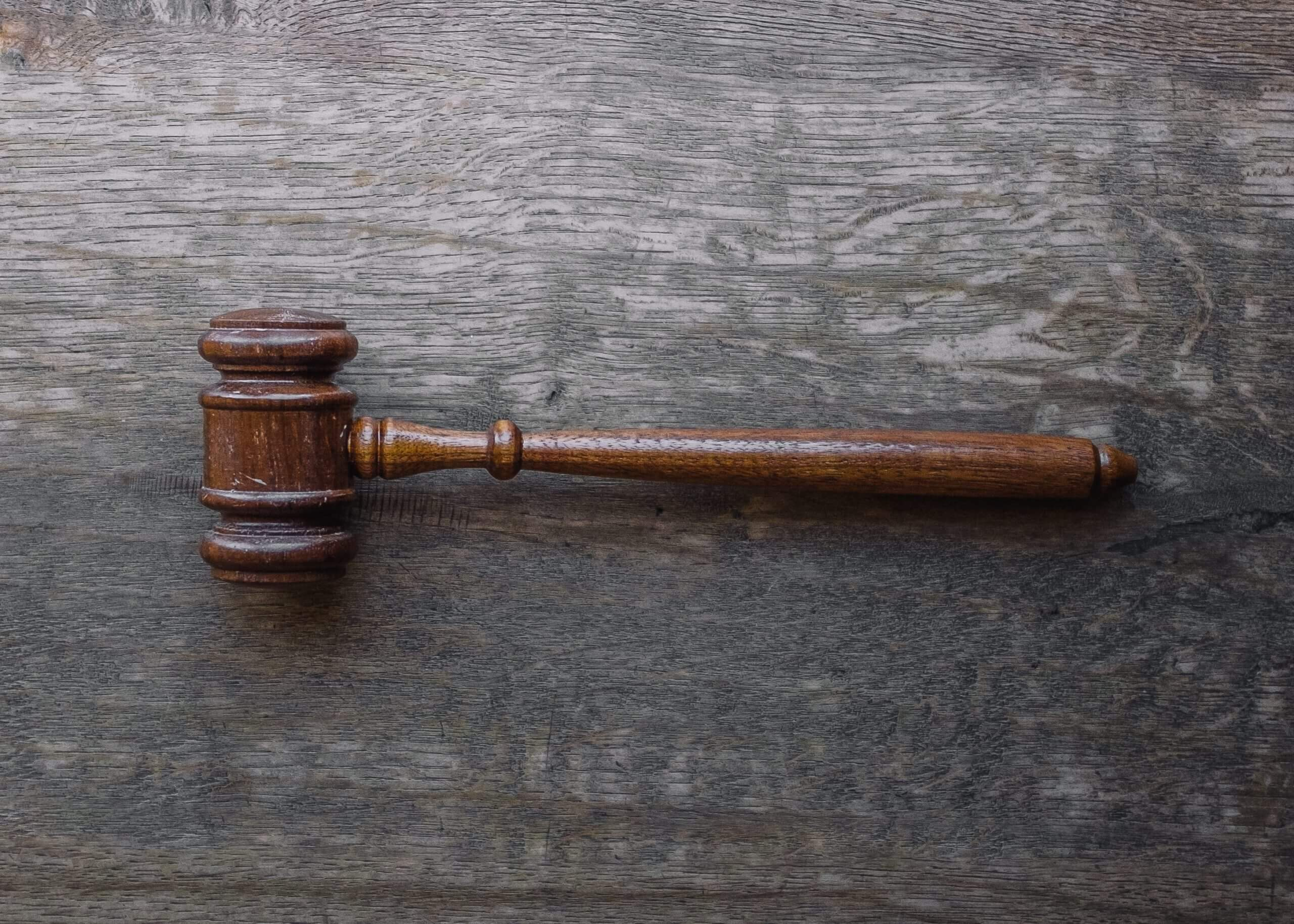 An old wooden gavel lying atop a wooden desk.