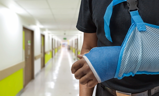 Close-up view of a person standing in a hospital hallway, with their arm in a cast and sling.