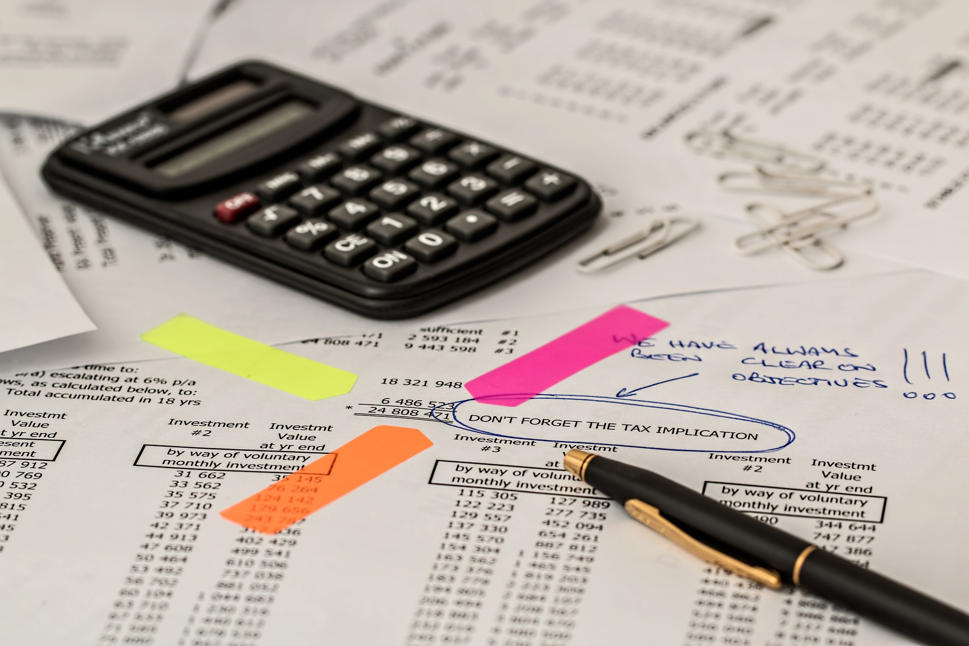 A monthly balance sheet that mentions tax implications with a calculator, pen, and colored adhesive markers.