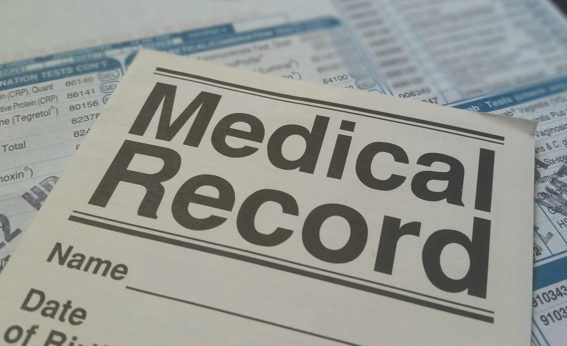 A medical record form laying on a pile of medical papers