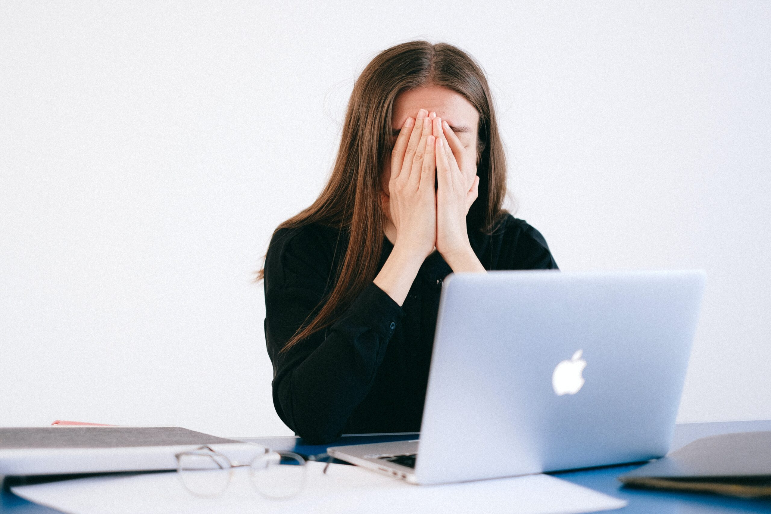 A stressed-out employee sits at a laptop with their face in their hands.