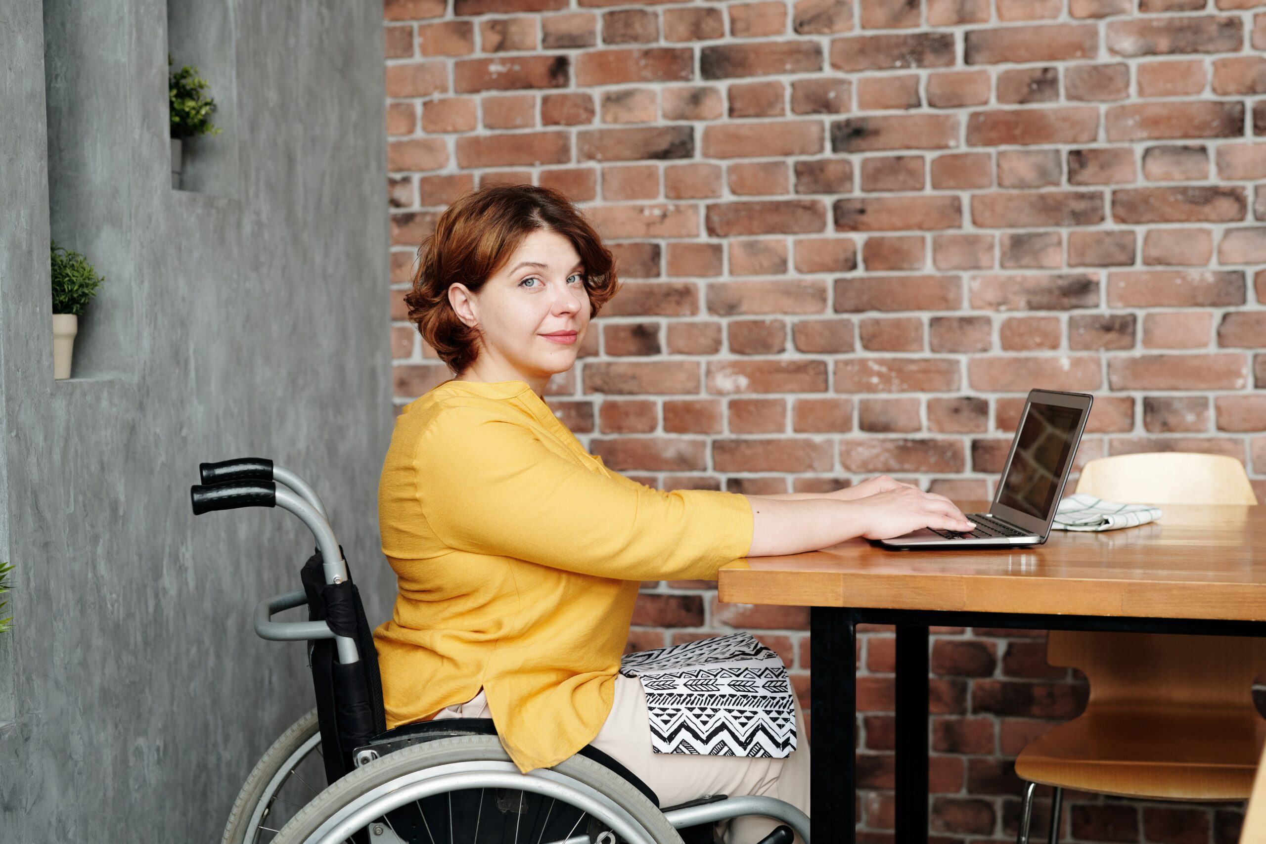 A person sitting in a wheelchair works on their laptop while looking at the camera.