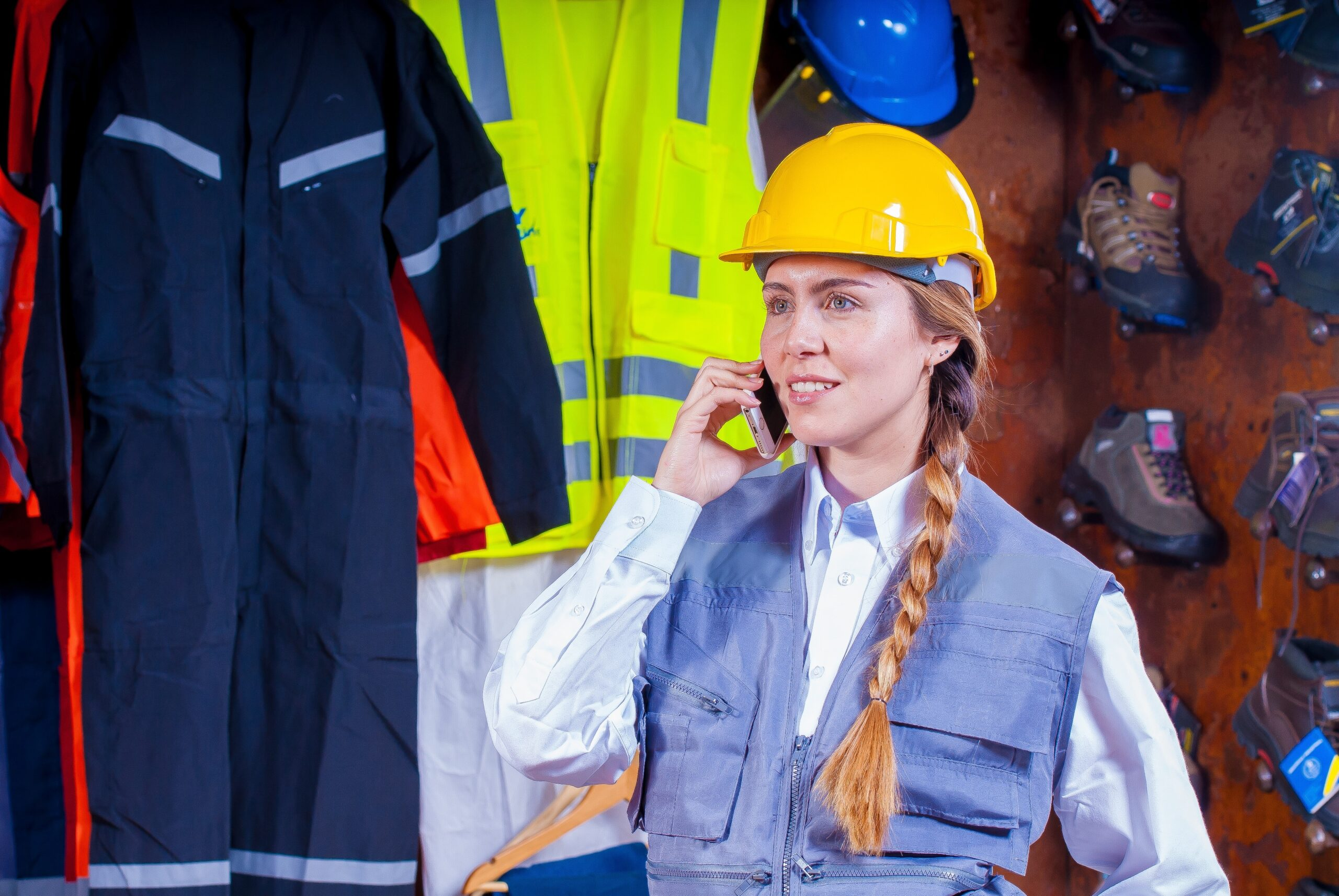 A person wearing a yellow hard hat talks on a cell phone and stands in front of workplace safety equipment.
