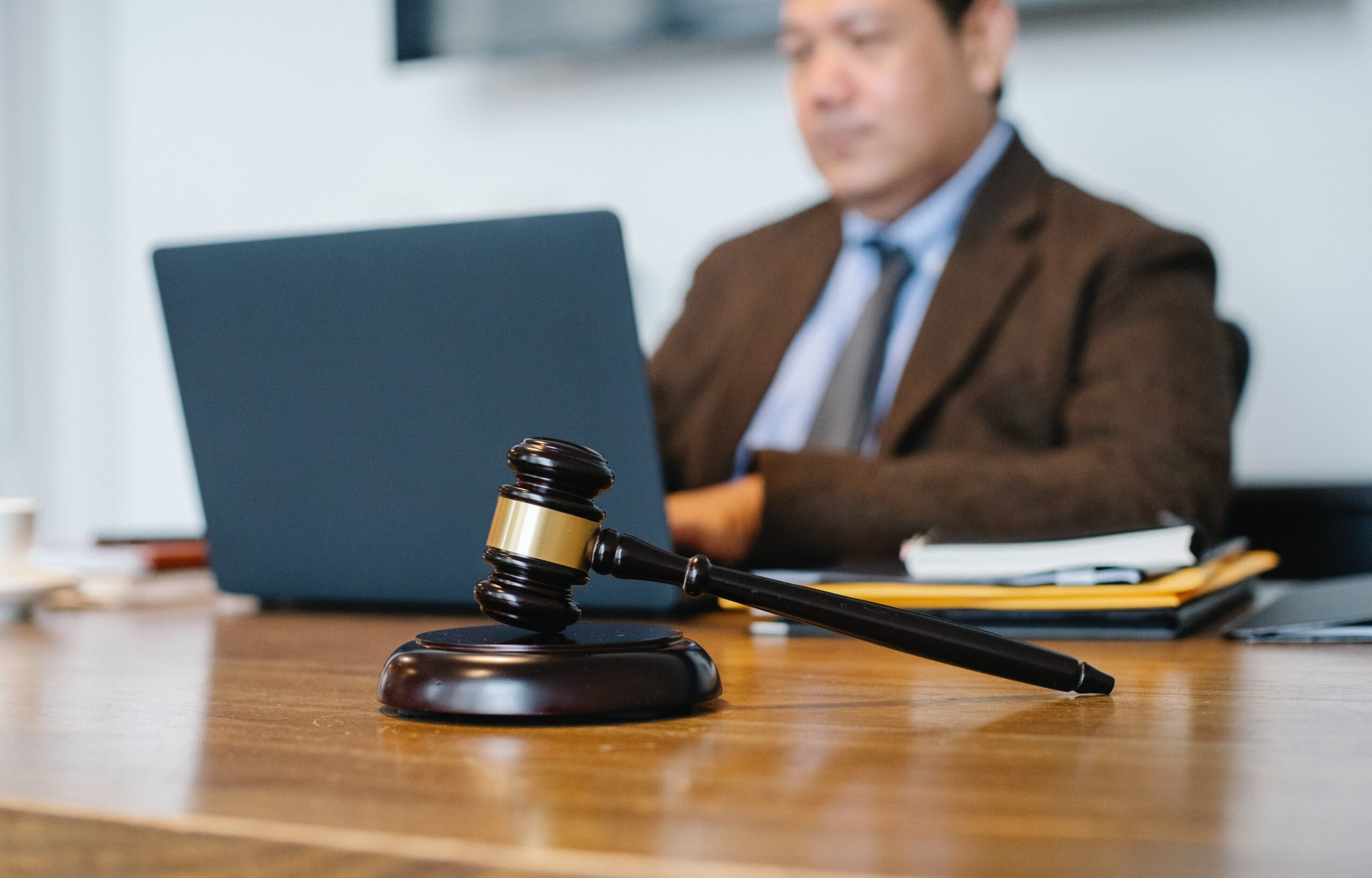 A gavel sits on a desk and an individual working on a computer is blurred in the background.