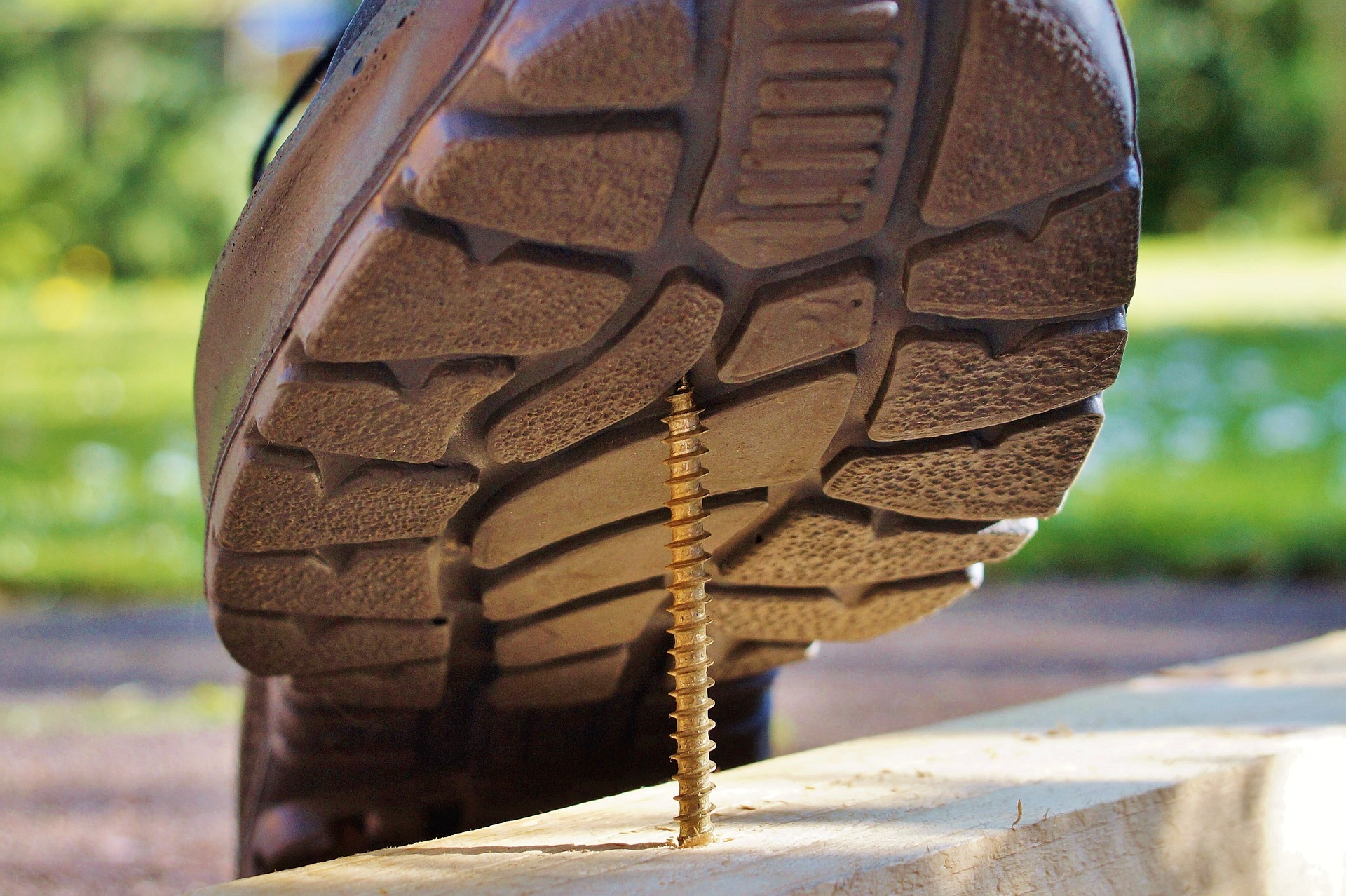 Close-up view of the underside of a person's shoe stepping on an exposed screw.