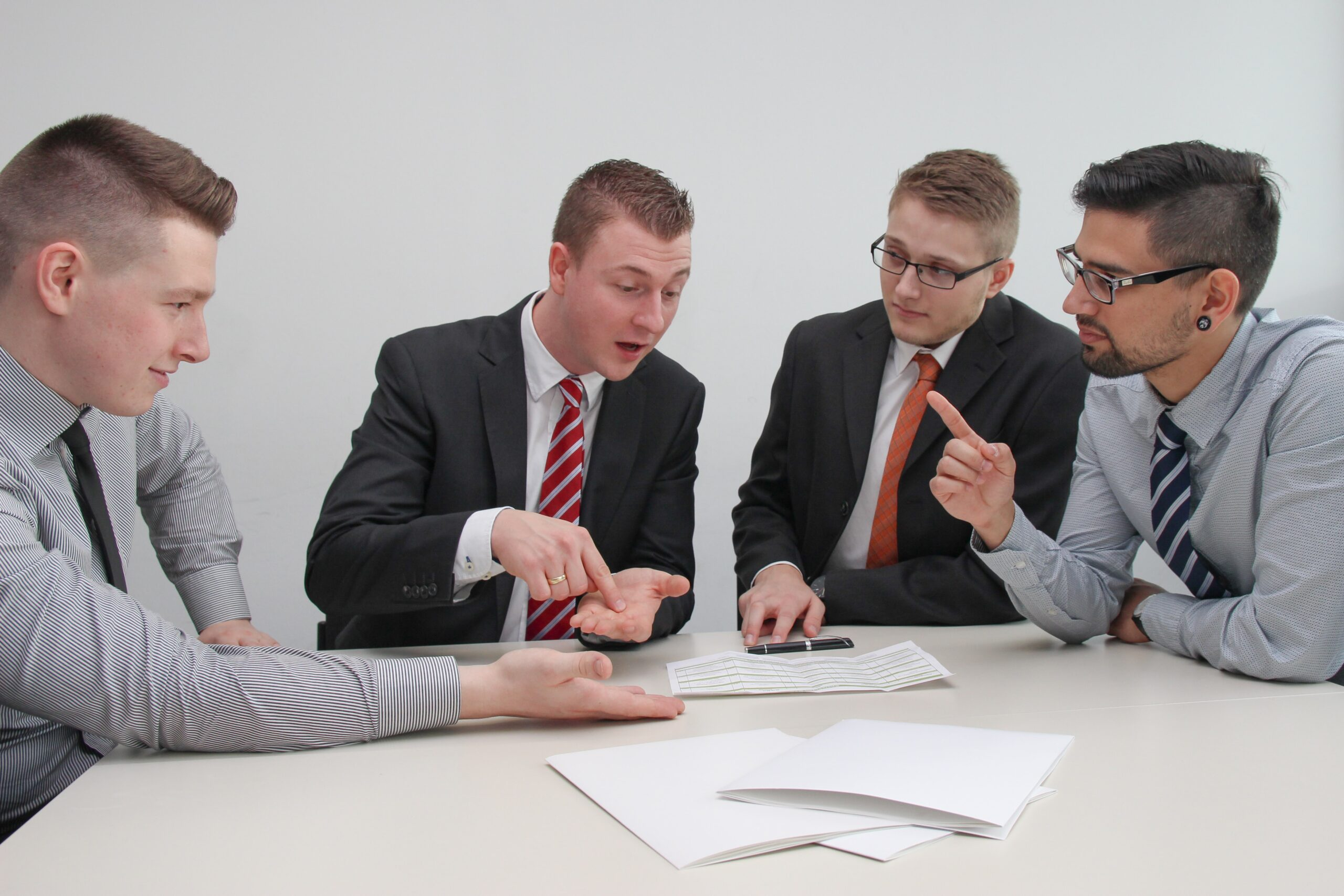 Four businessmen in a meeting with papers on a conference table.