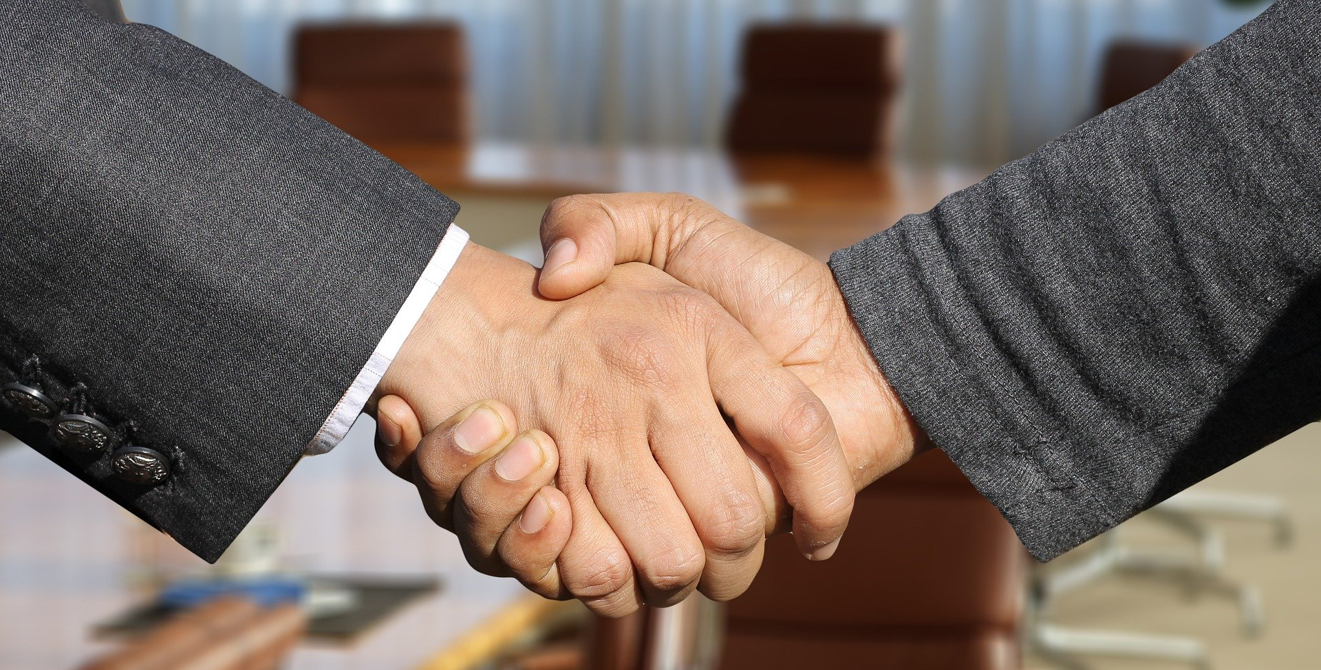 Two people in suits shaking hands with a meeting room in the background.