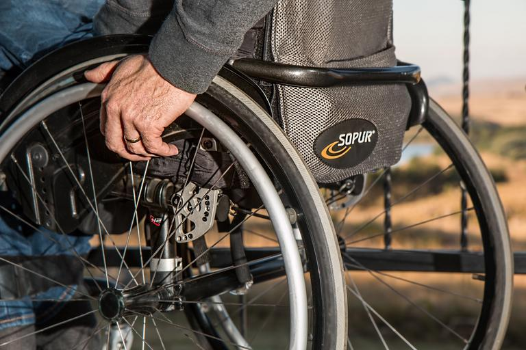 A close-up photo of a person sitting in a wheelchair with their hand holding the top of a wheel.