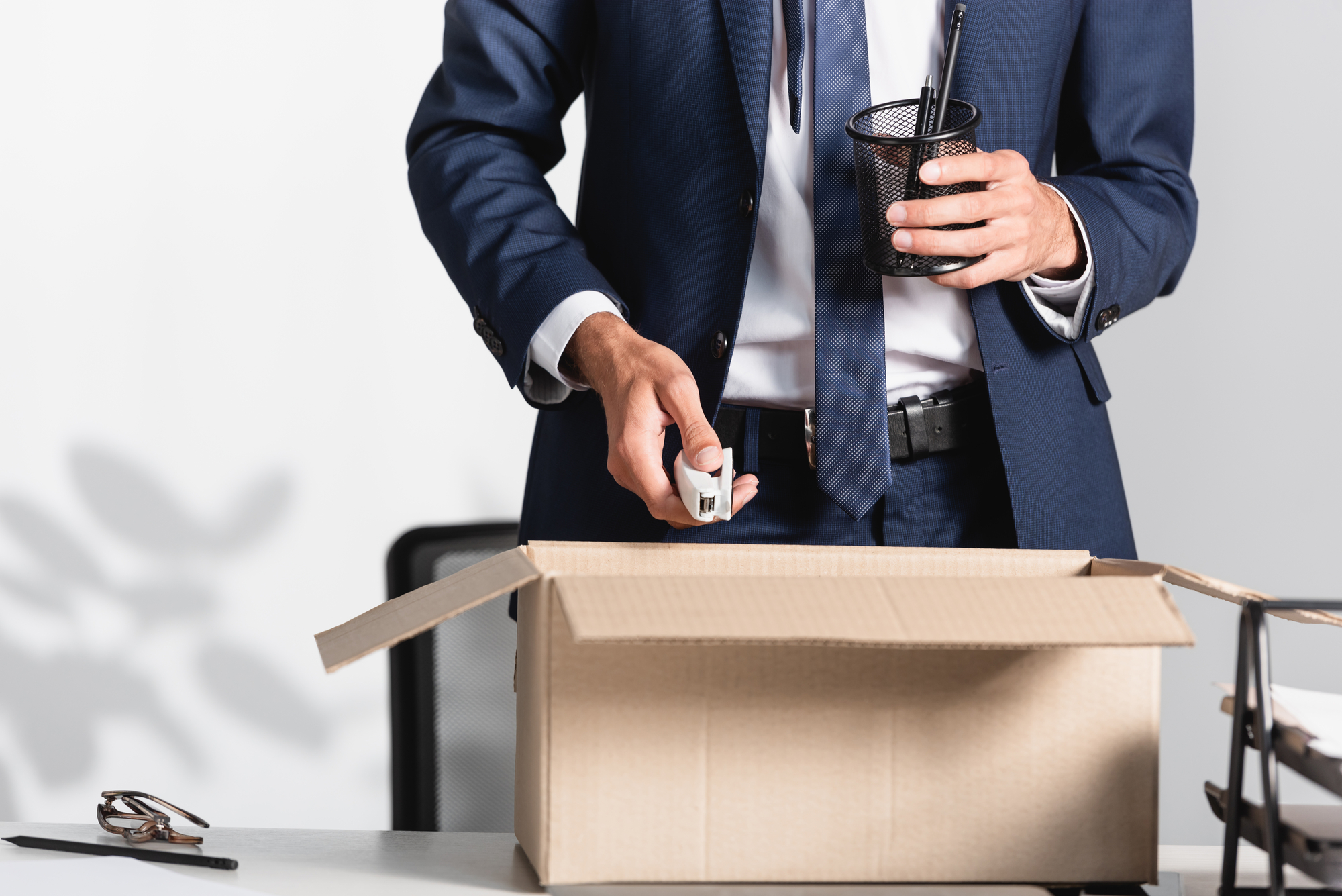 Medium shot of an individual in a business suit standing at a desk, placing personal items into a cardboard box as they prepare to leave the office after being terminated.