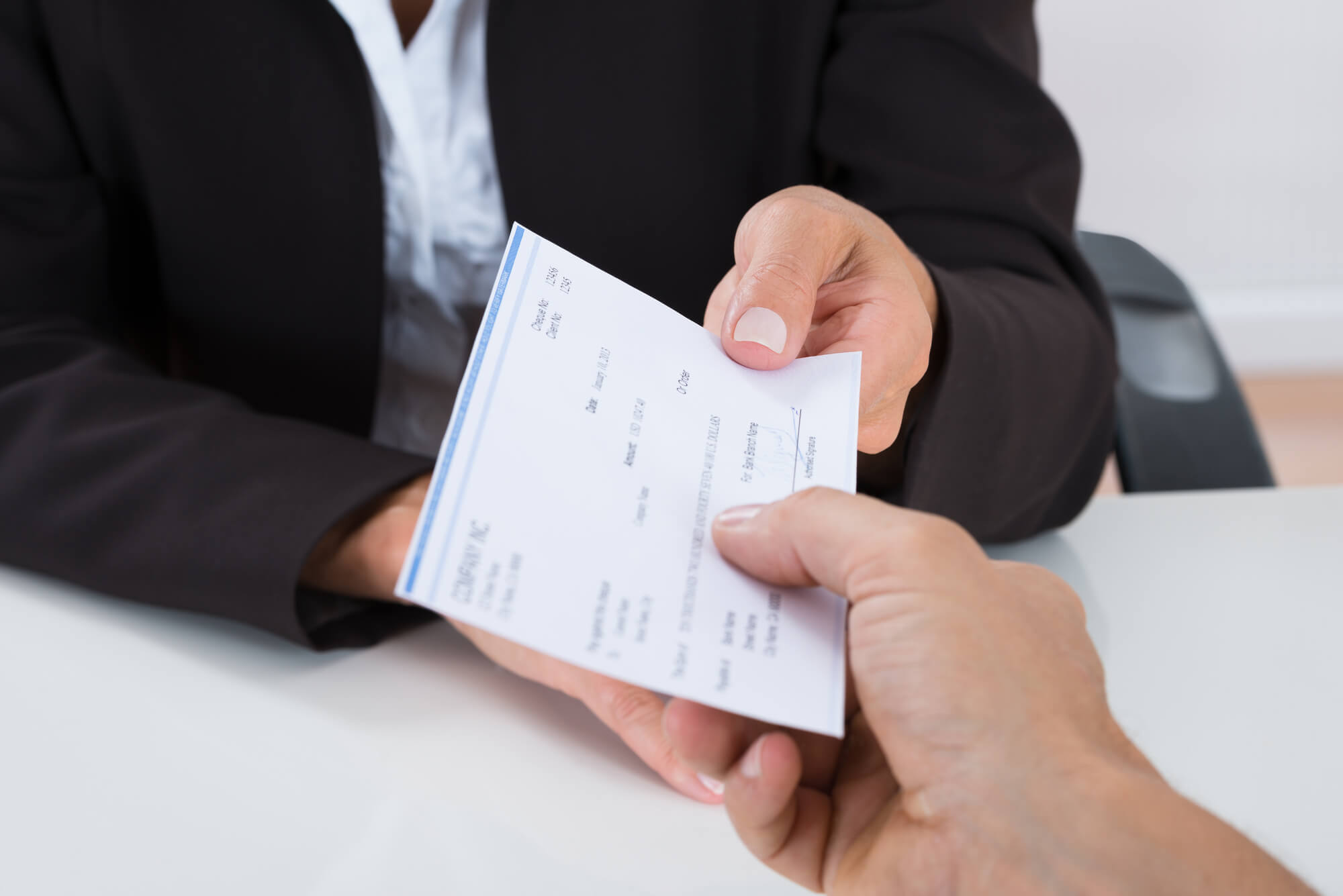 Close-up, first-person view of a hand reaching out to accept a paycheck being handed over by another person wearing a suit.
